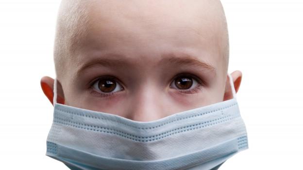 Ein Kindergesicht, Kopfhaare rasiert, mit Mundschutz.