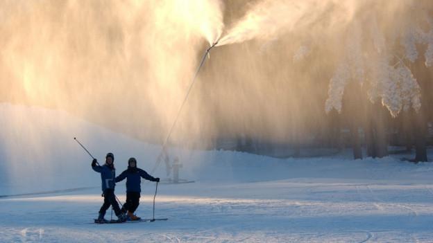 Im Gegenlicht des Sprühnebels von Schneelanzen stehen zwei Skifahrer auf einer Skipiste.