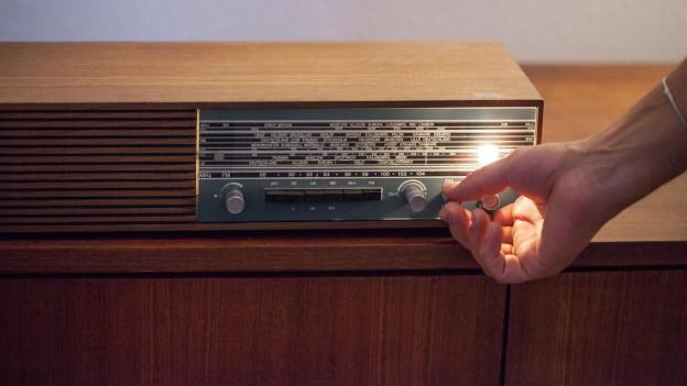 Jemand sucht auf einem alten Radio einen Sender.