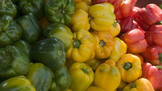Nahaufnahme einer Kiste voller grüner, gelber und roter Peperoni