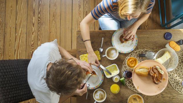 Zwei Personen essen am Tisch.