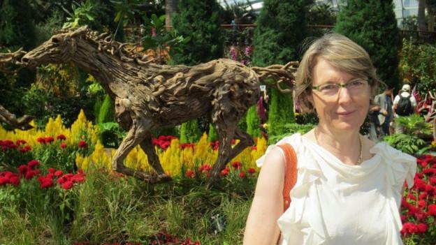 Sabine Silberstein trägt eine weisse Sommerbluse und steht in einem botanischen Garten. Im Hintergrund sieht man viele exotische Pflanzen.