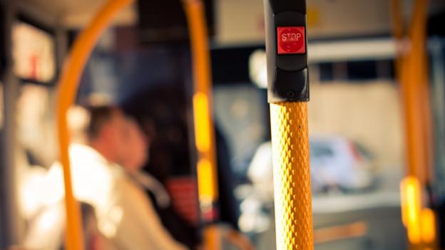 Innenaufnahme Bus. Stange mit roter Stop-Taste im Vordergrund.