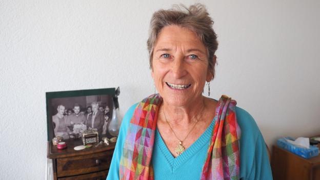 Ursula Hauser lacht in die Kamera. Im Hintergrund eine Fotografie mit ihrem verstorbenen Mann Antonio Grieco, in Begleitung von Che Guevara.