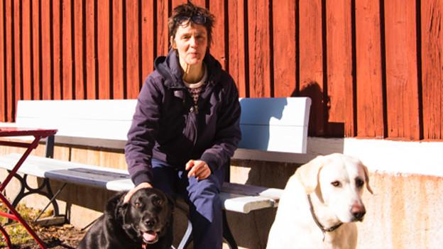 Cécile Dambach mit ihren zwei Hunden vor einer roten Holzhauswand.