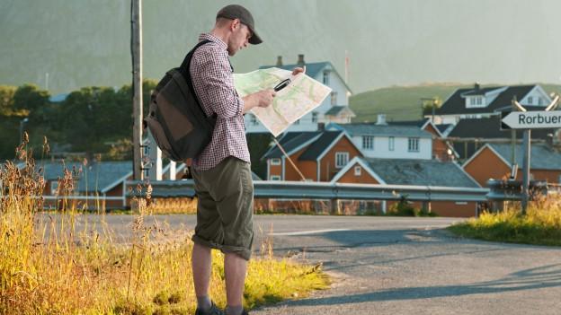 Mann steht an einer Kreuzung und studiert die Landkarte mit einer Lupe in der Hand.