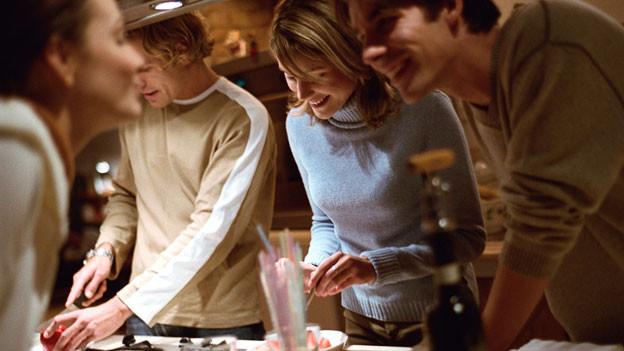 Vier Menschen stehen in der Küche und bereiten Speisen zu.