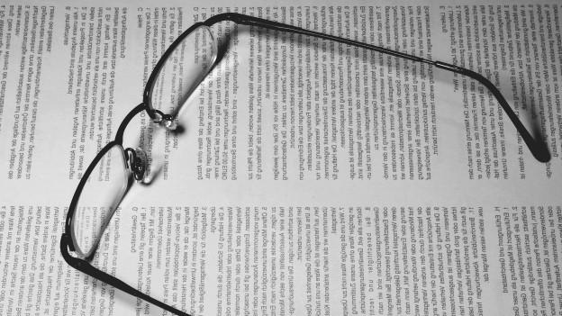 Ein unscharfer Blick auf ein Blatt Papier, eng beschrieben mit AGB, auf dem Blatt liegt eine Lesebrille