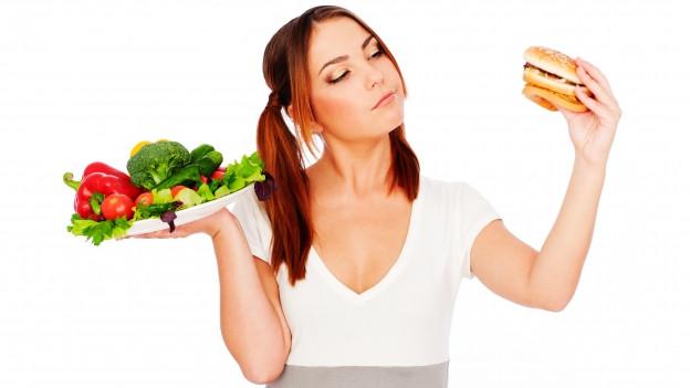 Frau begutachtet Hamburger und Gemüseplatte.