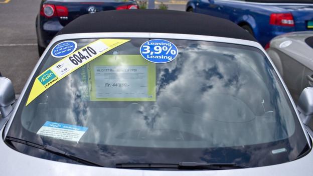 Frontscheibe eines Autos mit Leasing-Werbekleber drauf.