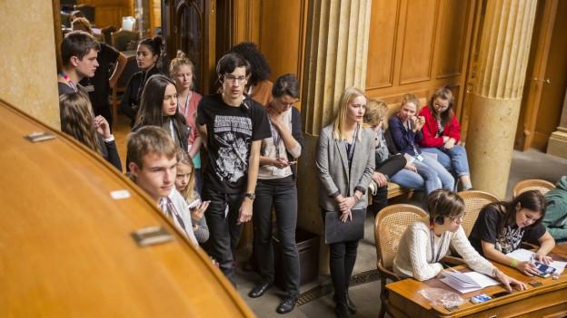 Nationalratssaal im Bundeshaus, von rechts laufen junge Frauen und Männer in den Ratssaal