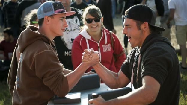Zwei Jugendliche messen sich im Armdrücken.
