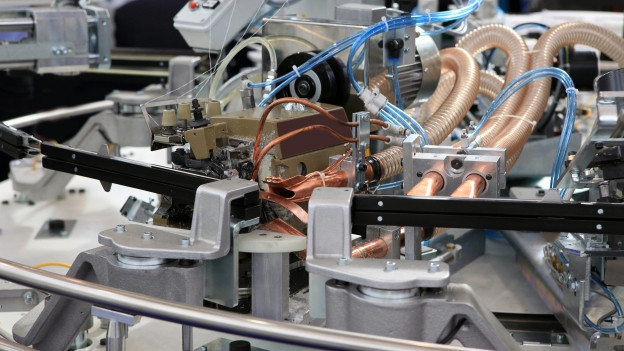 man sieht eine chromstahl-glänzende Maschine mit vielen Hebeln und blauen Fäden