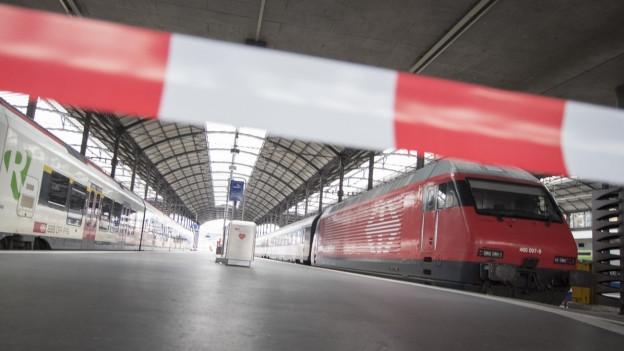 Zwei Züge im Bahnhof Luzern stehen still, im Vordergrund ein rot-weisses Absperrband.
