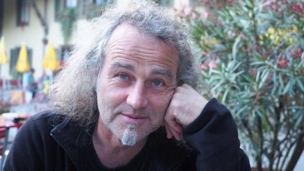 Porträt von Dänu Wisler mit kurzem Bart und langen Haaren.