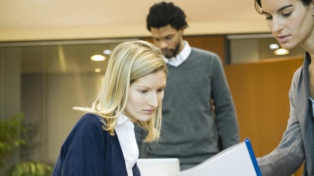 Frau sitz am Bürotisch und schaut in die Unterlagen einer Kollegin.