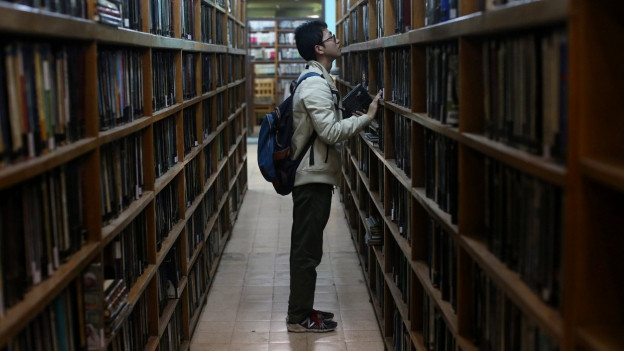 Mann steht ratlos vor Bücherregal.