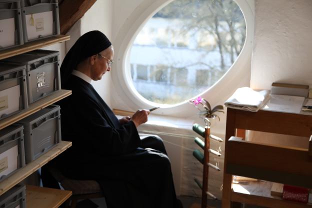 Nonne sitzt am Fenster.