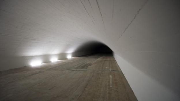 Blick in einen langgezogenen Stollen, die Gewölbewände weiss lackiert, der Boden holzbraun