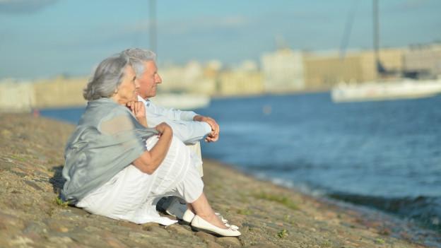 Ein älteres Ehepaar sitzt an einem steinigen Strand und blickt in die Ferne.