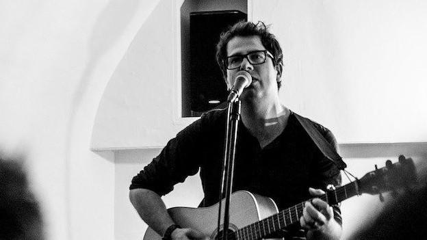 Curdin Nicolay, schwarz weiss Bild, mit Gitarre