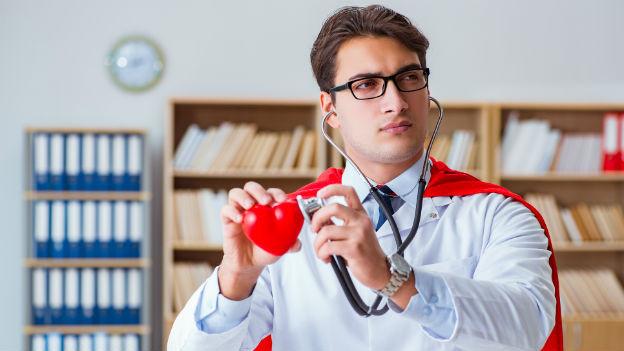 Arzt mit Superhelden-Cape untersucht ein Herz.