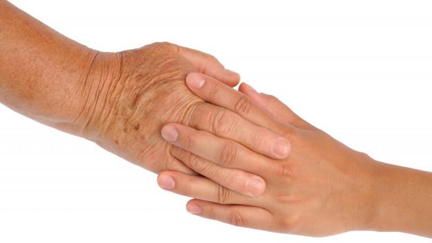 Eine junge Hand und eine alte Hand