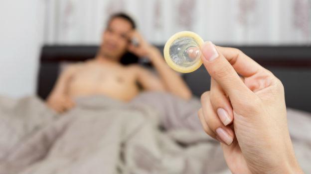 Frau hält Kondom in der Hand.