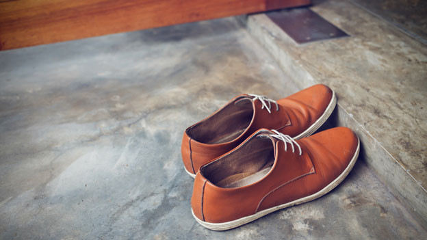 Schuhe steht vor einer Türschwelle.