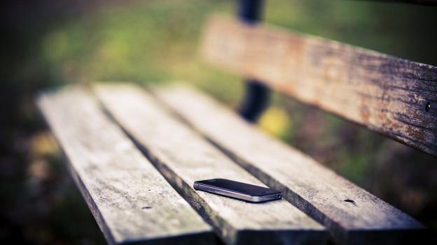 Ein Smartphone liegt vergessen auf einer Parkbank.
