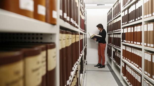 Frau steht im Gang eines Archivs zwischen Gestellen und sucht nach Akten
