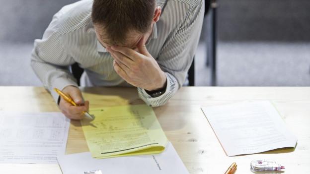 Mann sitzt am Tisch und beugt sich mit dem Stift in der Hand über einen Prüfungsbogen.