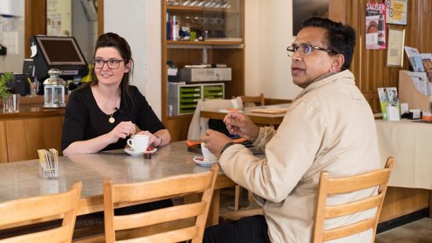 Die Wirtin Jeanine Schilder und der Wirt Brasad Bharanya sitzen an einem Tisch und lernen sich kennen.