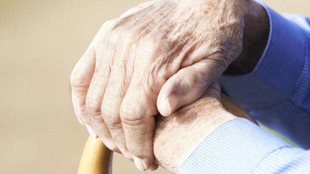 Blick auf ein paar alte, gefaltete Hände.