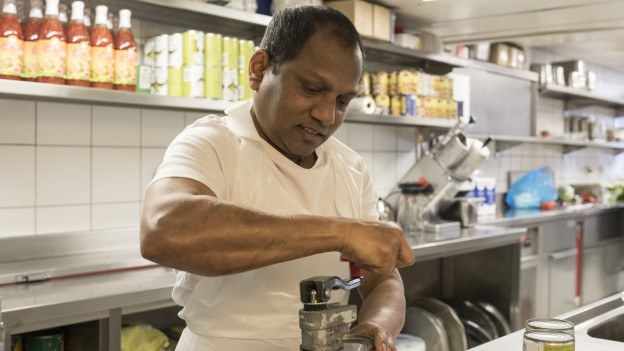 Ein Angestellter mit Migrationshintergrund in einer Küche.