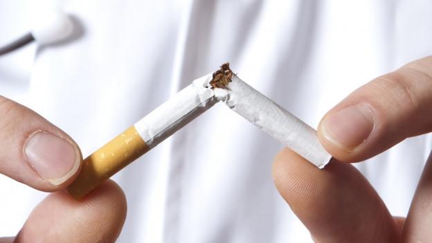 Mann verbricht Zigarette.