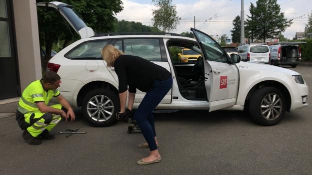 Redaktorin Pascale Folke platziert den Wagenheber unter dem SRF Auto.