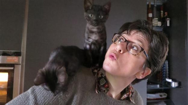 Susanne von Arx hat ihre kleine Katze auf der Schulter sitzen und schaut zu ihr hoch.