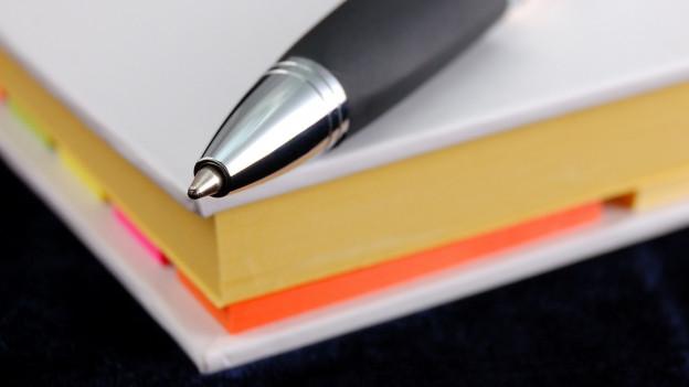 Kugelschreiber auf einem Buch.