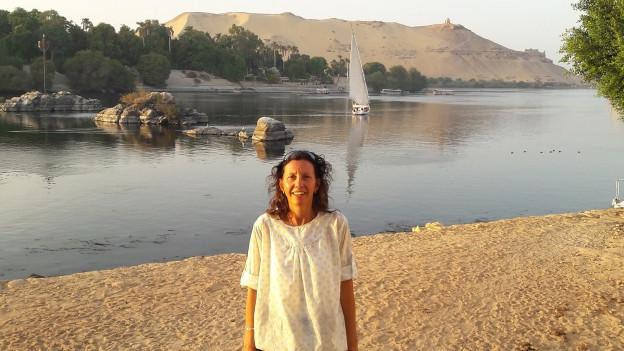 Olivia Keller steht an einem Fluss Nähe Kairo. Sie trägt ein weisses Hemd.