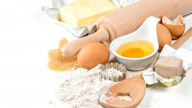 Mehl, Eier, Butter und Frischhefe auf einem Tisch