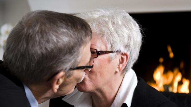 Ältere Frau und älterer Mann küssen sich.