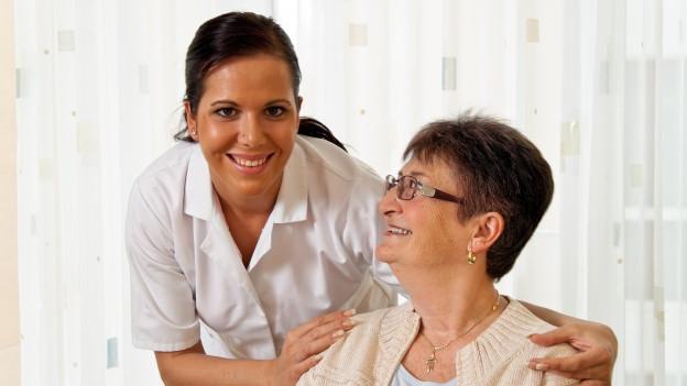 Eine lächelnde Pflegefachfrau nimmt eine Patientin in den Arm