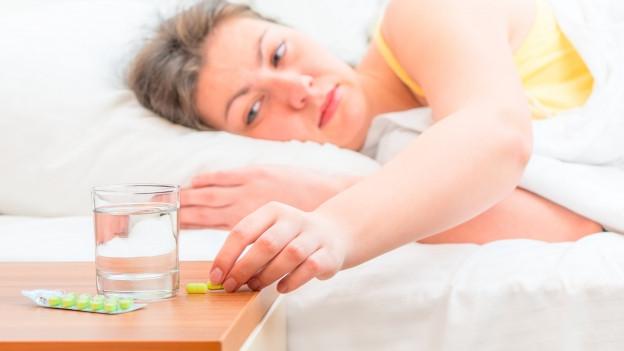 Ein Bett von der Seite her gesehen, eine Frau liegt darin in weissem Nachthem, den Blick aufs Nachttischchen gerichtet, wo ein Glas Wasser und zwei Päckchen mit Tabletten stehen.