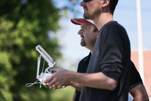 Zwei Männer bedienen eine Drohnenfernsteuerung.