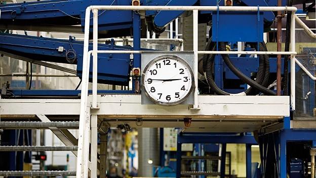 Eine Uhr hängt in einer Fabrik.