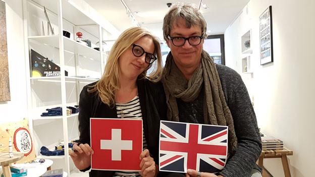 Porträt eines Paares, sie hält die Flagge aus der Schweiz, er jene aus Grossbritannien