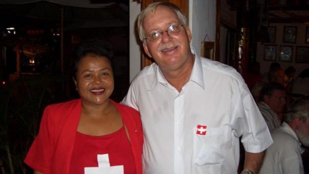 Jon P. Zurcher zusammen mit seiner balinesischen Frau Suci. Sie trägt ein rotes T-Shirt mit einem Schweizer Kreuz.
