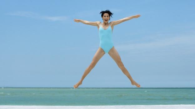 Eine Frau im blauen Badeanzug hüpft am Starnd in die Luft.