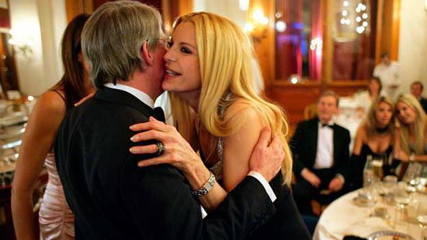 Mann begrüsst Frau mit einem Küsschen auf die Wange